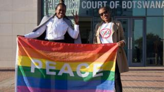 Activists pose with a rainbow flag as they celebrate outside Botswana High Court in Gaborone after the landmark ruling in June
