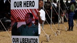 A woman holds a pro-Mugabe poster