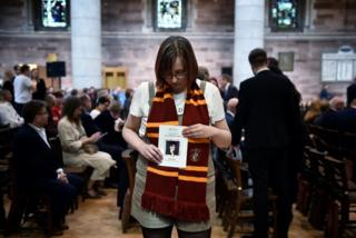 A friend of Lyra McKee holds an order of service as she attends the murdered journalist's funeral at St Anne's Cathedral in Belfast