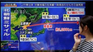 شابة يابانية تنظر إلى لقطة تلفزيونية توضح مسار الصاروخ الباليستي الذي أطلقته فوق جزيرة هوكايدو شمالي اليابان