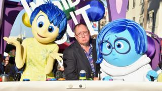 John Lasseter is pictured comically frowning in exaggerated sadness, seated between the characters of Joy and Sadness from Pixar's Inside Out