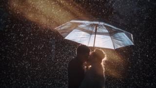 Casal se beija sob chuva e debaixo de guarda-chuve