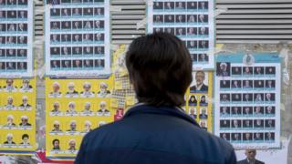 An Iranian man looks at election posters