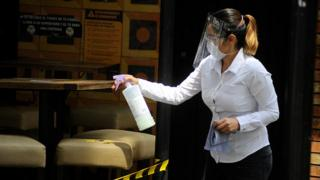 A hostess wears face shield while disinfect a place in a restaurant of Zona rosa in Mexico City