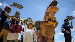 Активісти в костюмах і з банерами на акції протесту в Манілі
