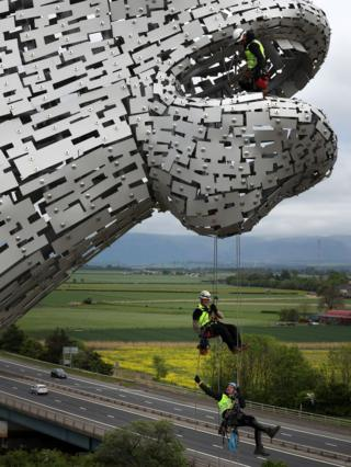 Men suspended from the Kelpies on wires