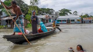 La gente viaja en barco en la zona inundada después de las fuertes lluvias monzónicas en Dohrar, cerca de Dhaka, Bangladesh