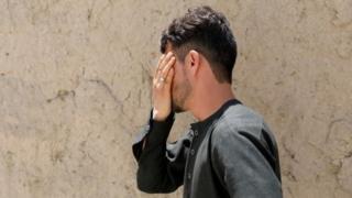 Mirwais Elmi cries covering his face