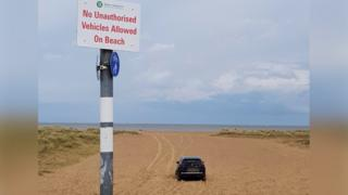 Car stranded in sand in Norfolk