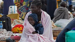 A woman from South Sudan holds a child on her knees as she sits inside a make-shift camp at Nimule border, in Amuru Distric in Uganda on 16 July 2016