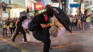 Pro-democracy protesters react as police fire tear gas during a demonstration on October 20, 2019 in Hong Kong, China