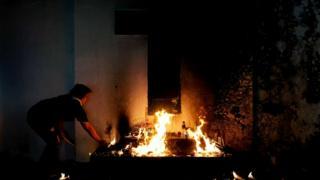 Женщина зажигает свечи на кладбище в Маниле (Филиппины) во время празднования Дня всех святых