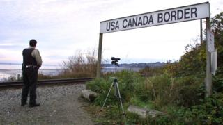 A Canadian Customs and Fisheries officer watches over the U.S.-Canada border between Blaine, Washington and White Rock, British Columbia November 8, 2001 in White Rock, BC. The Peace Arch border crossing is one of the busiest crossings in North America