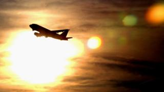 A plane is silhouetted against the sky as it takes off from Heathrow Airport 19 December 2002 in London, England.