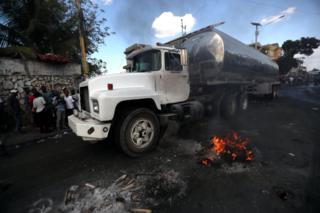 A truck with a fuel container travels along a blocked road during anti-government protests in Port-au-Prince