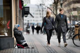 A woman begs as a smart couple walks past.