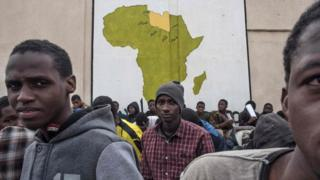 A picture taken on November 27, 2017 shows African migrants waiting outside in a courtyard at the Tariq Al-Matar detention centre on the outskirts of the Libyan capital Tripoli.
