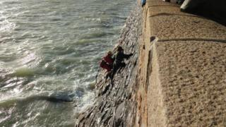 Firefighters rescuing teenagers cut off by the tide