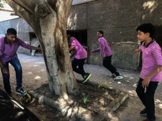Students play football in street at the end of the study day on September 24, 2018 in Cairo, Egypt.