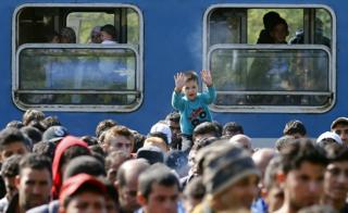 Migrants walk from train at Hegyeshalom, Hungary, to border with Austria