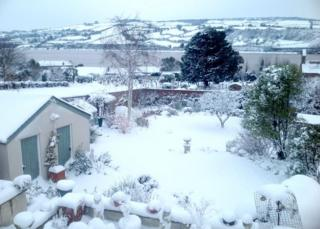 A garden covered in snow with rolling snow-covered hills in the background