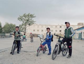 Boys sit on their bikes