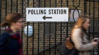 Two women walk past a polling station