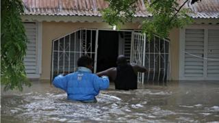 People enter a home during the floods caused by the passage of Storm Laura in Azua, Dominican Republic August 23, 2020.