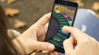 A woman using an online gambling website on her smartphone