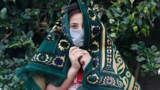 in_pictures A young Palestinian wearing a face mask holds a prayer mat over their head