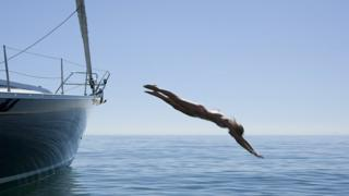 Девушка прыгает в воду с яхты