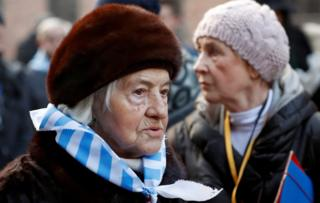 Holocaust survivors walk through the grounds of former German Nazi death camp Auschwitz