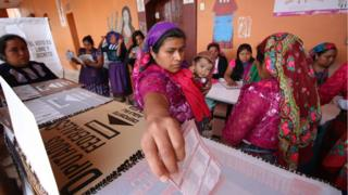 A woman holding a baby casts her ballot at a polling station during the presidential election in San Bartolome Quialana, in Oaxaca state, Mexico, July 1, 2018.