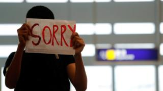 An anti-extradition bill protester offers an apology to passengers blocked from entering the security gates during a mass demonstration after a woman was shot in the eye, at the Hong Kong international airport
