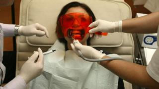 Woman having teeth-whitening procedure