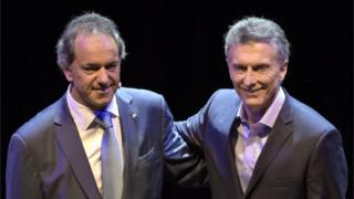Daniel Scioli (left) and Mauricio Macri embrace before a debate in Buenos Aires on 15 November, 2015, ahead of next November 22 run-off election.