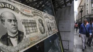 People walk past a bank's branch decorated with images of old Argentine peso bills, in Buenos Aires, on September 26, 2018.