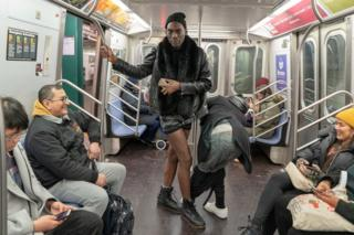 Two men ride a New York City subway line during the 18th annual No Pants Subway Ride