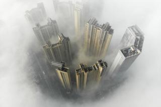 Vue aérienne de bâtiments entourés d'un épais brouillard