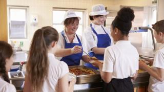 Pupils being served dinner