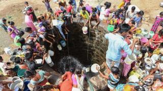 Personas sacando agua de un pozo.