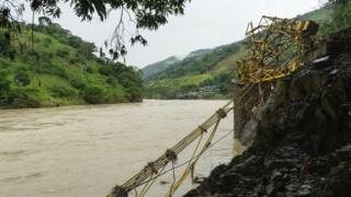 Twisted metal lies by the bank of the river Cauca