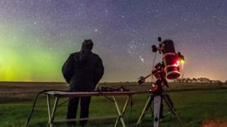 Pessoa observa o céu à noite ao lado de luneta