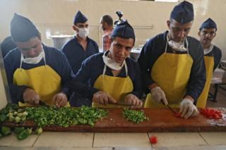 Prison inmates chop vegetables in a kitchen