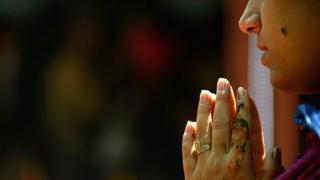 कश्मीर घाटी के खीरभवानी मंदिर में पूजा करती एक कश्मीरी पंडित महिला की तस्वीर