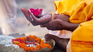 Sacred flowers are taken for worship on hand at river Ganges