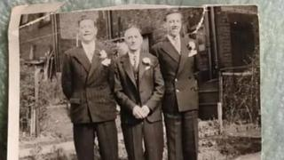 Black and white photo of three men in wedding suits