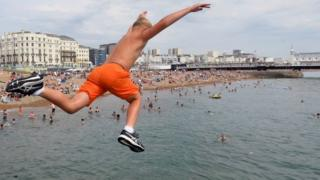 sports A boy jumps into the sea as he enjoys the hot weather at Brighton beach