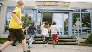 Crianças correm para entrar em um edifício, onde está escrito 'Grundschule' (escola primária, em alemão)