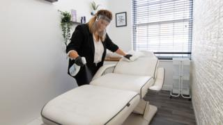 Clare Gleadell cleans and disinfects surfaces at Beautique beauty salon in Loughborough as they prepare to reopen on Monday